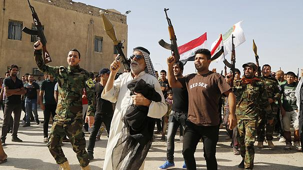 """Shi'ites take up arms to battle Sunni Muslim insurgency."" (Iraq 2014)"